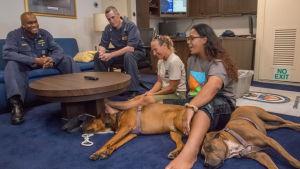 Tasha Fuiava (till höger) och Jennifer Appel (till vänster på golvet) och deras hundar Zeus och Valentine ombord på USS Ashland som räddade dem.