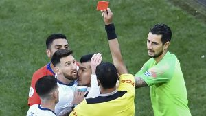 Domaren visar det röda kortet åt Messi, som är mitt i ett gruppbråk.