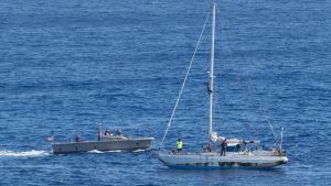 En båt från USS Ashland intill segelbåten,  innan kvinnorna togs ombord.