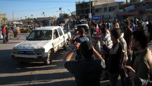 Väpnade män paraderar på gatorna efter strider med irakiska styrkor.