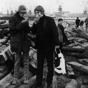 Nuoria miehiä 1960-luvulla seisomassa puupölkkyjen päällä kaupunkimaisemassa. Hattupäinen mies vasemmalla syö omenaa.