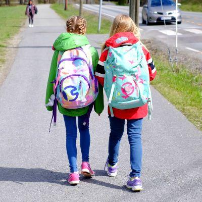 Skolbarn går längs trottoar