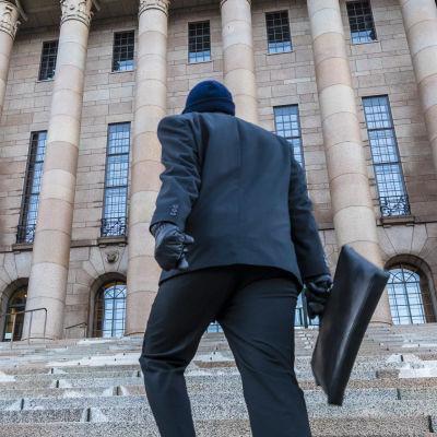 En person i svarta kläder och väska går upp för trapporna till riksdagshuset i Helsingfors.