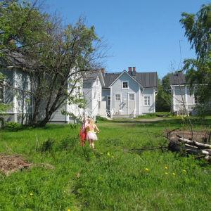 Pieni tyllihameinen tyttö kesäisellä pihamaalla, etualalla ruohikkoa ja taka-alalla puutalopihapiiri.