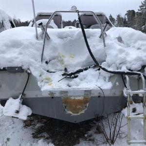 En båt täckt av snö där utombordsmotorn har tagits bort.