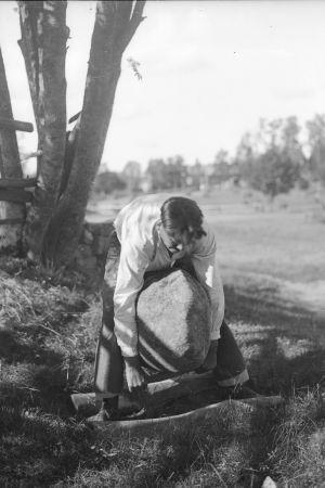 En man lyfter en stor sten med sina armar. Bilden är tagen 1932 i Terjärv, Risbacka.