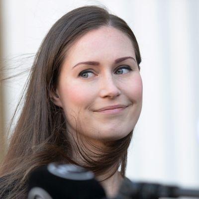 SAnna Marin tittar eftertänksamt leende på Annika Saarikko som är i färd med att förklara något inför mikrofoner.