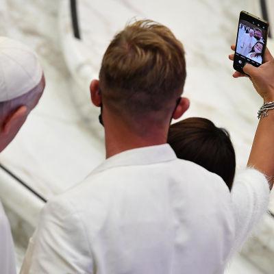 Pariskunta ottaa paavin kanssa selfien.