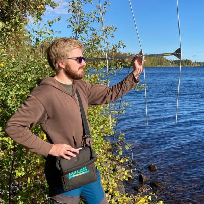 Luonnonvarakeskuksen tutkija Riku Rinnevalli kuuntelee antennin avulla radiolohien liikkeitä Kemijokivarressa