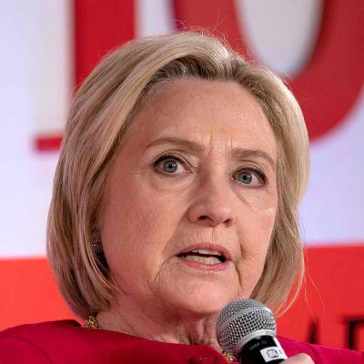Porträtt på Hillary Clinton som talar i en mikrofon.
