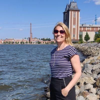 Kvinna står vid havet och ler mot kameran.