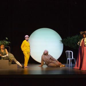Fyra skådespelare i granna kläder står på en scen med en stor rund lampa i bakgrunden.