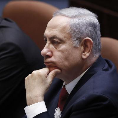 Benjamin Netanyahu sitter med handen mot hakan.
