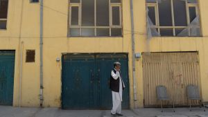 En afghansk man talar i telefon utanför det hus som attackerades i Kabul den 21 maj 2017.  En tyska kvinna och en afghansk vakt dödades medan en finländsk kvinna kidnappades.