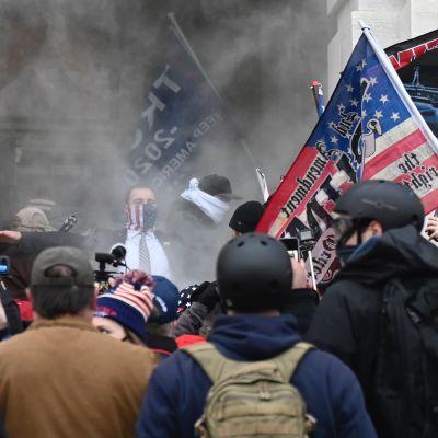Trump-anhängare i ett moln av tårgas utanför Capitolium onsdagen den 6 januari.
