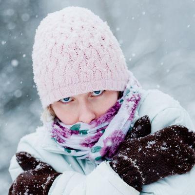 Kvinna som står ute i snöfall och fryser.