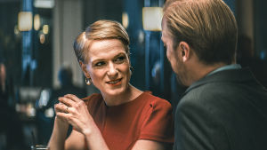 Karaktären Anna snyggt är uppklädd och ler mot en man.