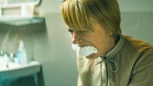 Anan sitter på en toalett och biter hårt kring hoprullat WC-papper..