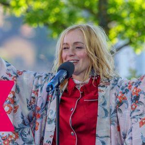 Lisa Ekdahl sträcker upp händerna medan hon leende sjunger i en mikrofon.