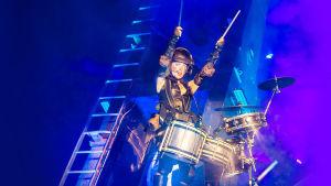 Vicky O'neon svävar i luften med trummor live på Glastonburyfestivalen.