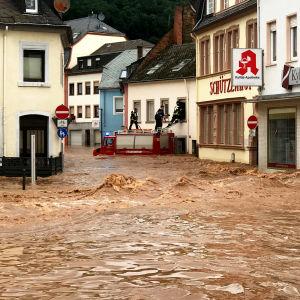 Räddningspersonal rör sig inne i en stad i Tyskland i översvämningar.