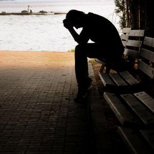 En pojke sitter på en parkbänk och lutar huvudet i händerna.