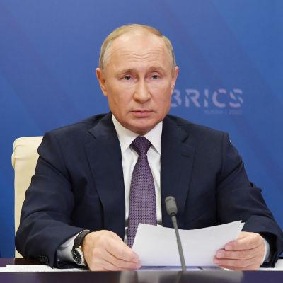 Rysslands president Vladimir Putin sitter vid ett bord med papper framför sig och en blå bakgrund med texten Brics. Putin deltar i Brics-ländernas virtuella toppmöte den 17 november 2020. Brics består av Brasilien, Ryssland, Indien, Kina och Sydafrika.