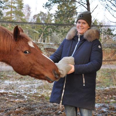 En brun häst sniffar på den kardade biten ull som Jessica håller i handen.