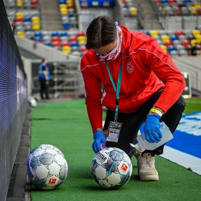 En bollkalle ser till att bollarna i matchen mellan Fortuna Düsseldorf och Paderborn hålls rena.