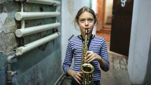 Polina spelar saxofon i ett källarutrymme.