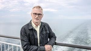 Henrik Meinander står på ett Sverigebåtdens däck.