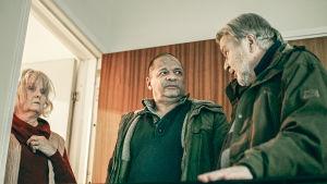 Nainen ja kaksi miestä seisovat ovensuussa sarjassa Myrskyn jälkeen.