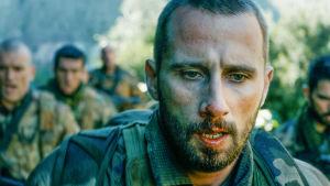 Mies lähikuvassa, nenästä vuotaa verta. Takana muita sotilaita.