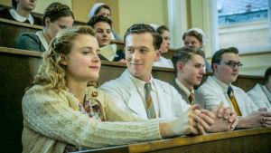 Opiskelijoita istumassa auditoriossa. Yksi mies katsoo vieressään istuvaa naista. Nainen hymyilee mietteliään näköisenä.