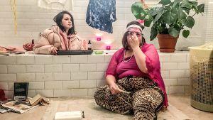 Kaksi naista kylpyhuoneessa. Toinen istuu kylpyammeessa ja toinen kylpyammeen edessä. Molemmilla on vaatteet päällä, toisella tupakka suussa.