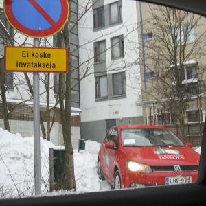 Privat foto av Anita Andersson på en bil från husets servicebolag som parkerat där hennes taxi ska stanna.