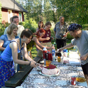 Kesäisessä puutarhassa pitkän pöydän äärellä joukko ihmisiä jonottaa vadelmakermakakkua.