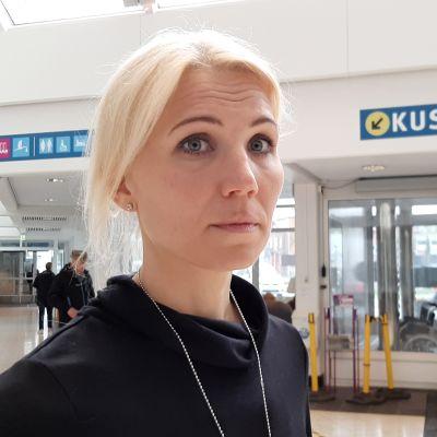 Marina Kinnunen är direktör för Vasa sjukvårdsdistrikt. Här står hon klädd i svart vid huvudentrén på Vasa centralsjukhus.