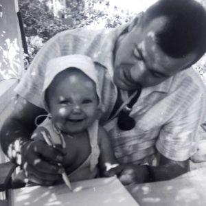 Minna Pyykkö kotiverannalla isän sylissä vauvana.