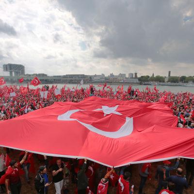 Demonstranter breder ut på en stor turkisk flagga samtidigt som hundratals andra viftar på mindre turkiska flaggor under en stöddemosntration för Turkiets president Erdoğan i Köln.