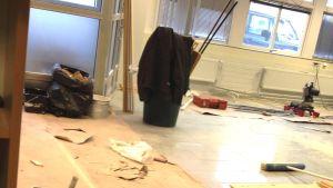 Byggarbetsplats inomhus, kontor byggs om, verktyg och virke på golvet, sopsäckar, papp täcker en del av golvet.