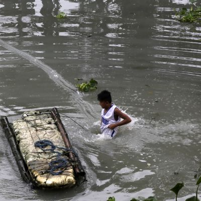 En filippinsk pojke leder en provisorisk flotte i ett översvämmat område i södra Manila.