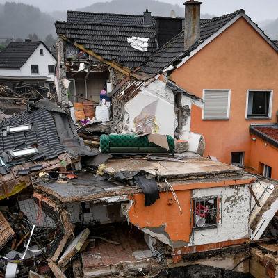 Ett hus har rasat i översvämningen. En grön sammetssoffa står på taket, antagligen har rummets väggar rasat.