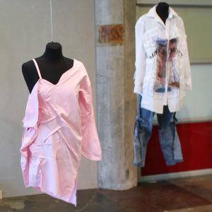 En rosa assymetrisk skjorta hänger på en svart provdocka , i bakgrunden andra provdockor med kläder på