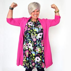 en gråhårig kvinna i färgglada kläder som håller upp händerna