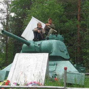 Pojkar med vit flagga i hand på en rysk stridsvagn i Sammatus).