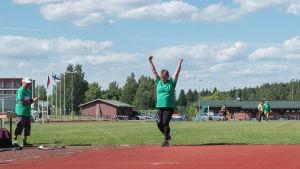 nainen nostaa kätensä ilmaan heittonsa jälkeen urheilukentällä.
