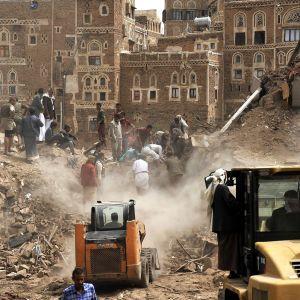 Ihmiset tutkivat raunioita pommituksen jäljiltä Jemenin vanhassakaupungissa. Etualalla on iso ja pieni maansiirtokone.