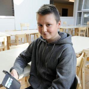 Jan-Arvid Sjöblom, elev i Oxhamns skola i Jajobstad, sitter med sin mobil i matsalen