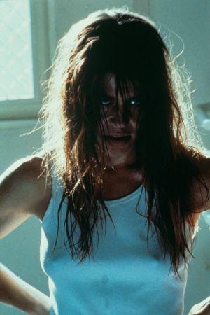 Närbild på Sarah Connor (Linda Hamilton) med rufsigt hår och vild blick.